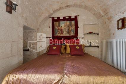 Double bedroom under the vaulted ceiling of a trullo
